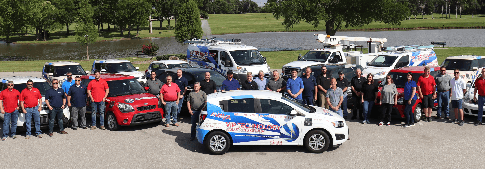 a photo of employees arranged around a branded fleet of vehicles in front of a scenic pond